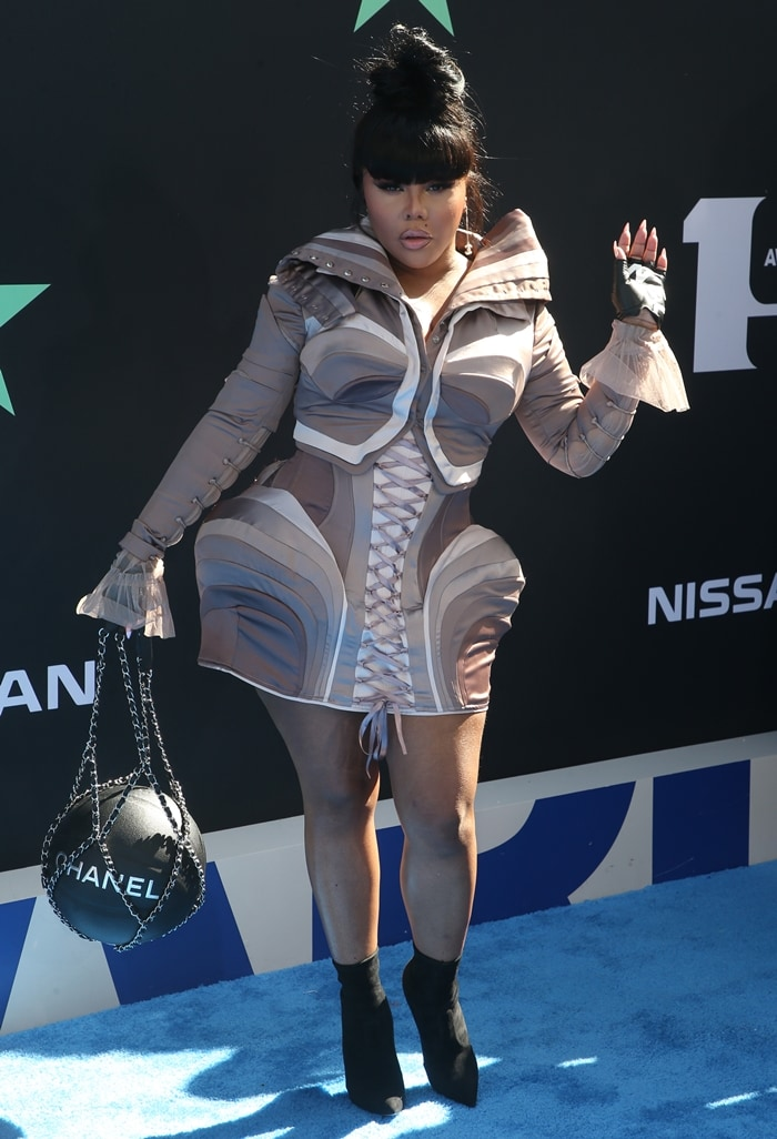 Lil' Kim flaunts her legs while toting a basketball Chanel purse
