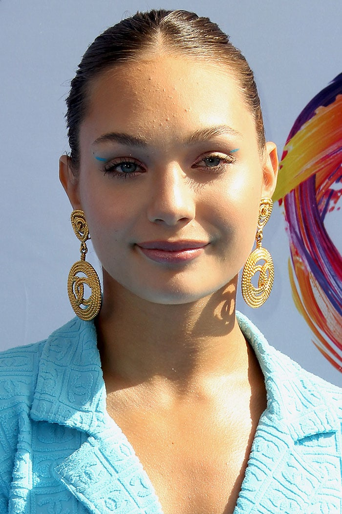 Maddie Ziegler wearing gold Chanel logo disc earrings and blue eyeliner streaks