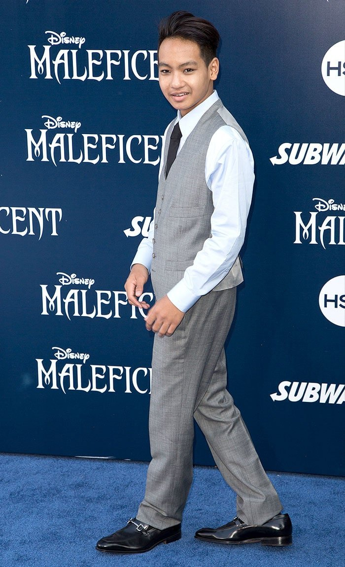 Maddox Chivan Jolie-Pitt in a gray suit and black loafers at the Maleficent premiere