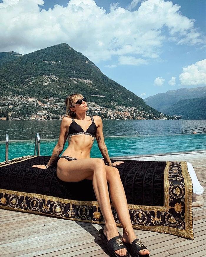 Miley Cyrus in a Versace bikini, sunglasses, and slides