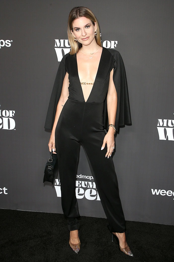 Rachel McCord in a black caped jumpsuit and sweaty clear pumps
