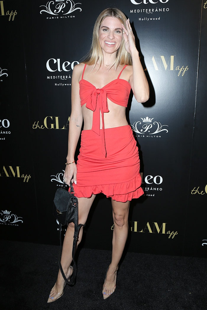 Rachel McCord in a red tie-front bra, red miniskirt and sweaty clear pumps