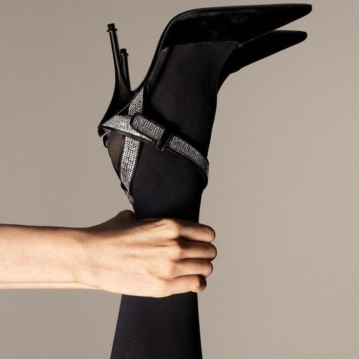 Velvet Asymmetric Crystal Pump features an asymmetric crystal strap and a satin-covered heel
