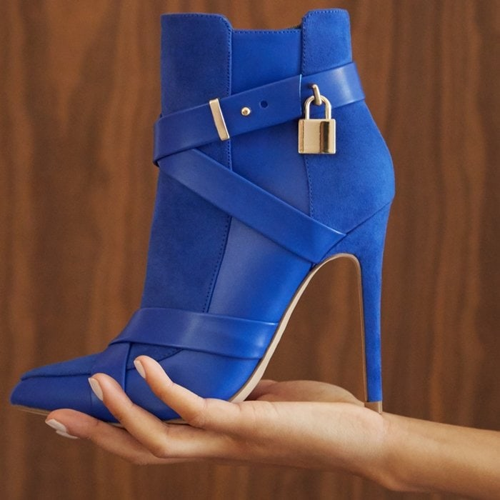 A pointed-toe bootie featuring a stiletto heel, wraparound buckle strap with a decorative lock, and side zipper closure.