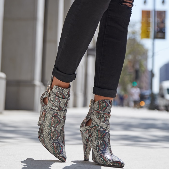 A bootie featuring a cone heel, side cutouts, wraparound buckle strap, and zipper closure.