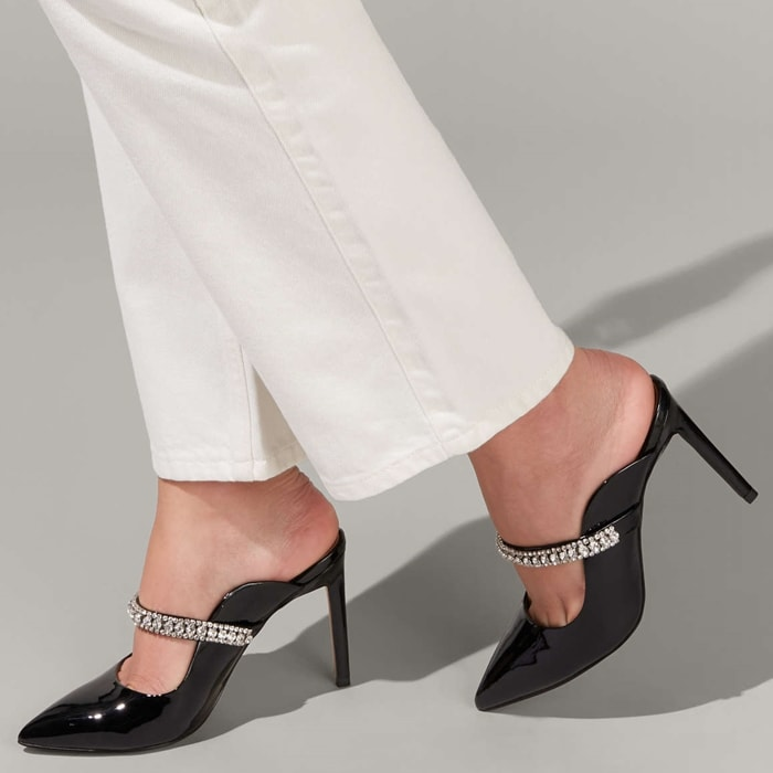 A strap glinting with crystals adds event-ready glamour to a leather mule with a pointy toe, curvy topline and slim stiletto heel