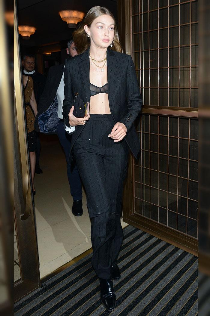 Gigi Hadid in a black mesh bra and a Ralph Lauren glitter pinstripe pantsuit