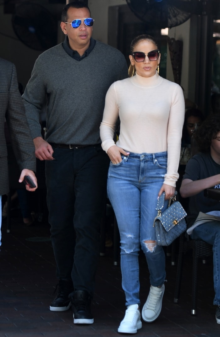 Jennifer Lopez wearing a pink sweater and jeans and boyfriend Alex Rodriguez are seen leaving lunch at Green Streets Cafe