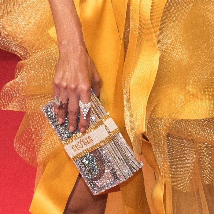 Jennifer Lopez toted a Judith Leiber Couture hard clutch bag in stacked money silhouette