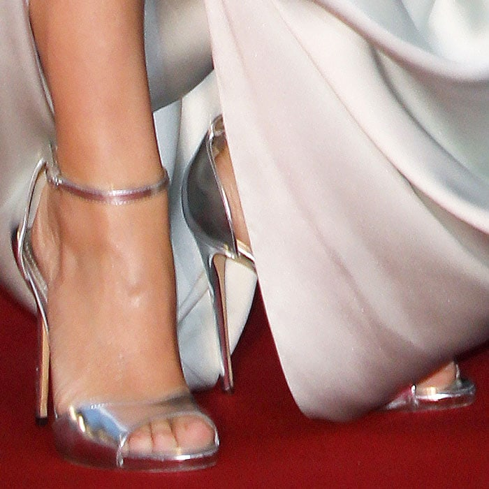 Closeup of the Dolce & Gabbana silver ankle-strap sandals on Kylie Minogue