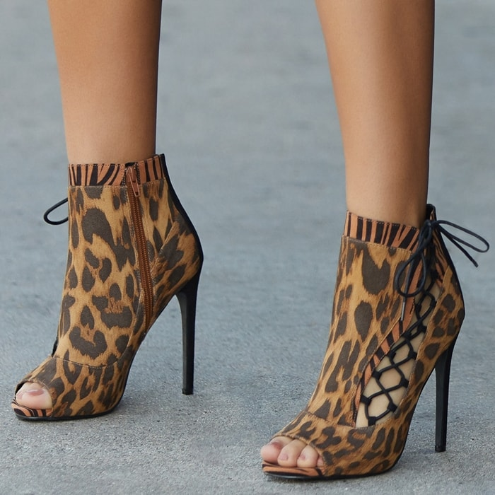A peep-toe stiletto bootie with a side cutout, lace-up detail, and back zipper closure.