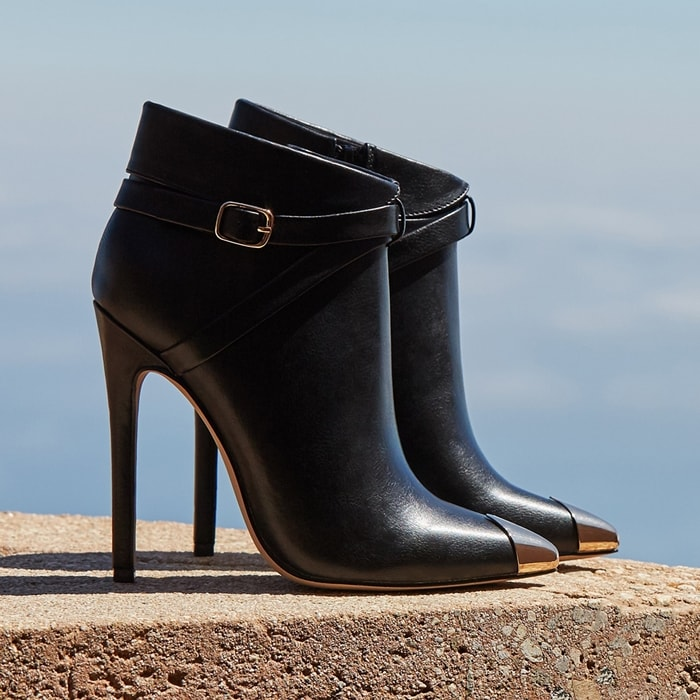 A stiletto-heeled bootie with a shiny cap toe, wraparound buckle strap, and zipper closure