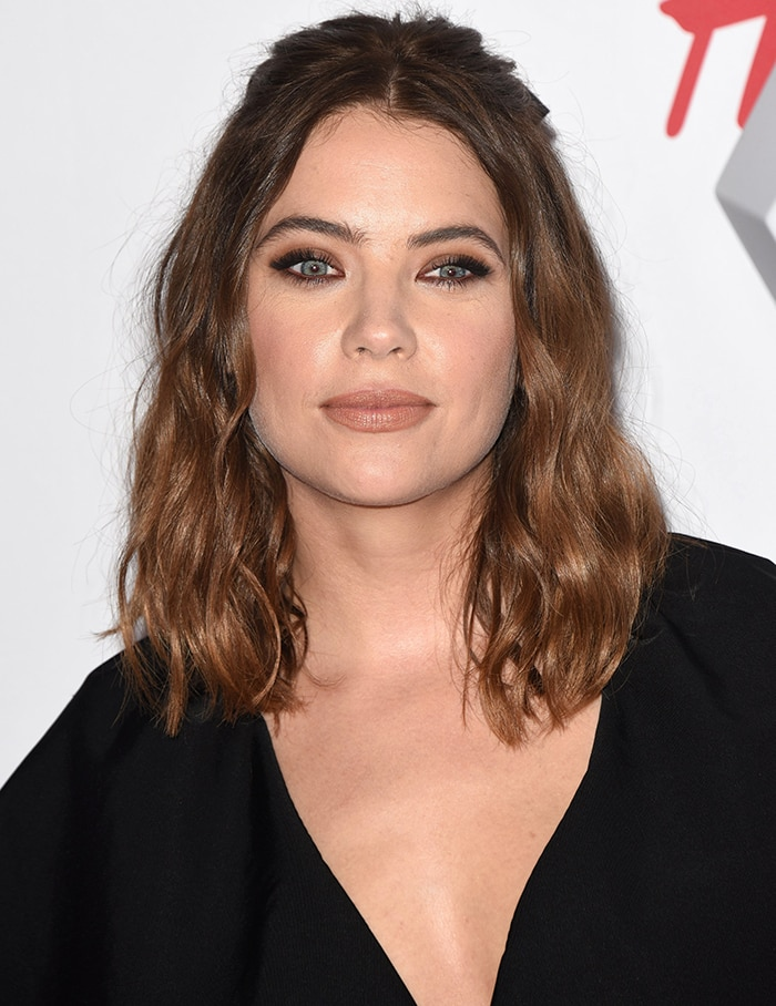 Ashley Benson wears her shoulder-length brown tresses in loose curls and sports nude makeup with smoky eyeshadow