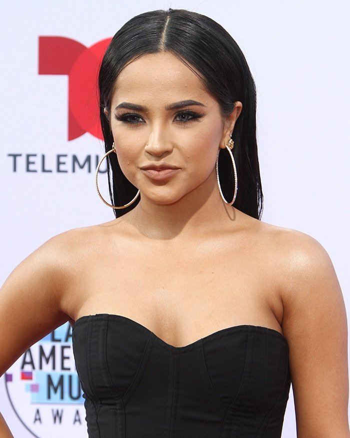 Becky G wears her long black hair sleek straight and parted in the middle