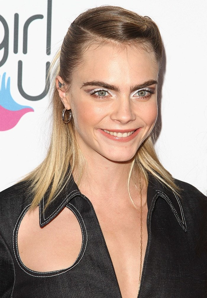 Cara Delevingne wears her shoulder-length blonde hair in a twisted half-up half-down style and sports a sweep of silver eyeshadow and peach lip shade