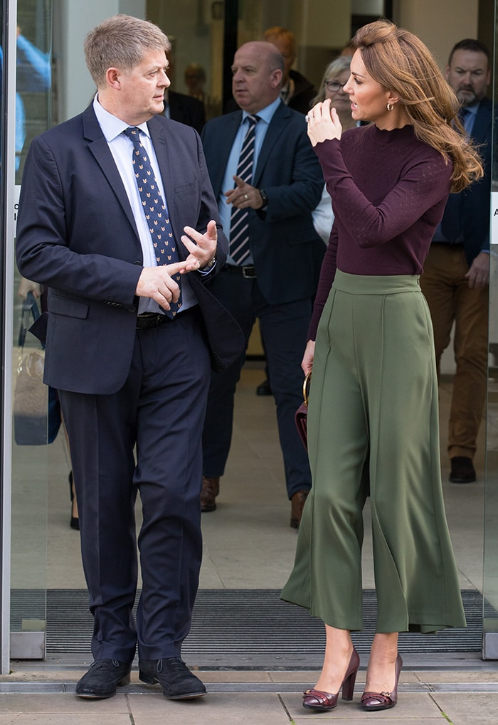 The Duchess of Cambridge wearing berry-colored sweater and olive culottes