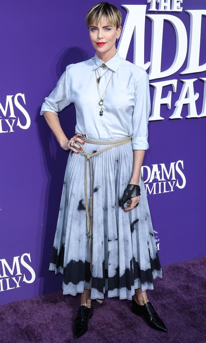 Charlize Theron styled a pleated tie-dye skirt with black pointy shoes