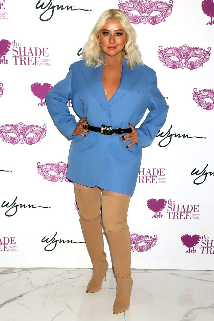 Christina Aguilera in a belted blue blazer dress and flesh-tone boots