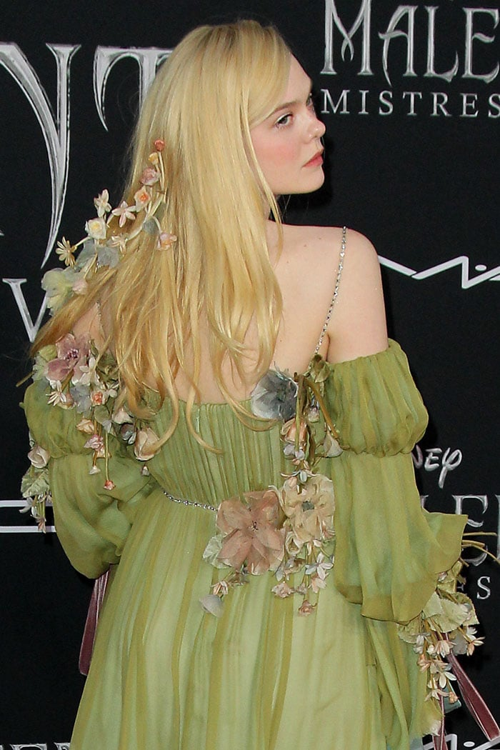 Elle Fanning with flowers in her blonde hair and Gucci gown