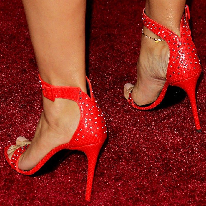 Heidi Klum's feet in red Giuseppe Zanotti snake-embossed sandals with grommet studs