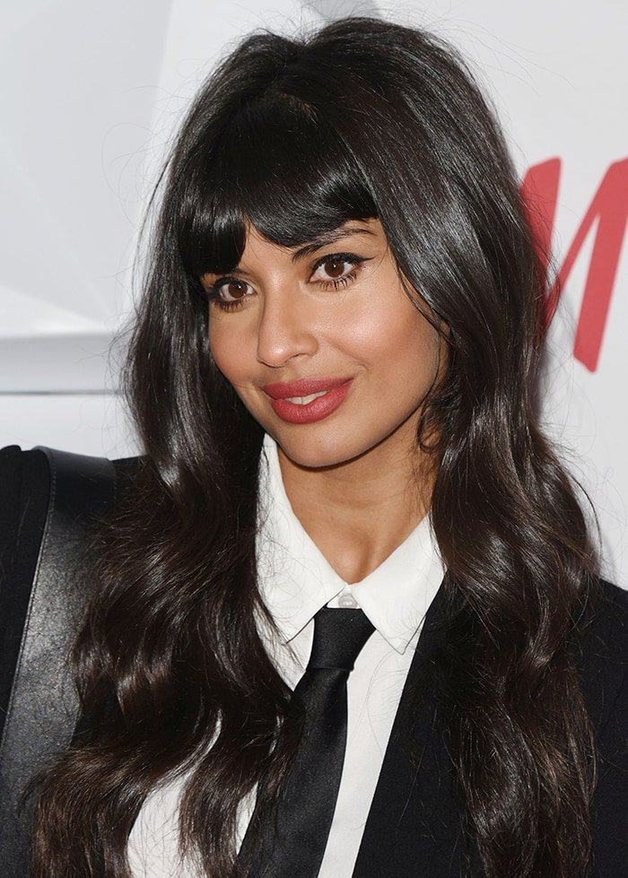 Jameela Jamil wears red lipstick and dark eye make-up, and styles her long black fringe hair in soft waves