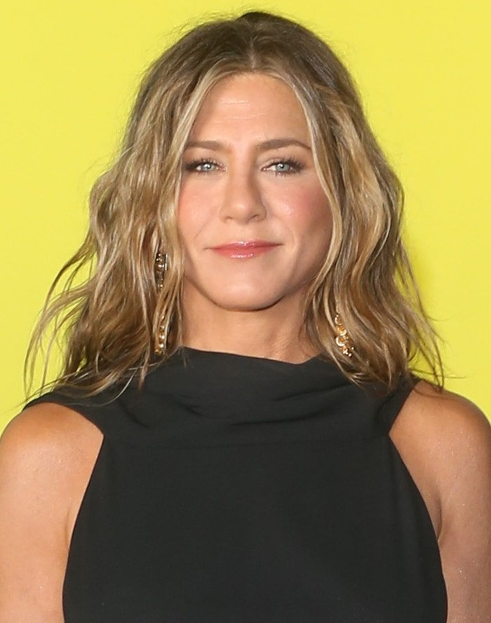 Jennifer Aniston wears her blonde hair in loose beach waves and sports pink blush and lip gloss