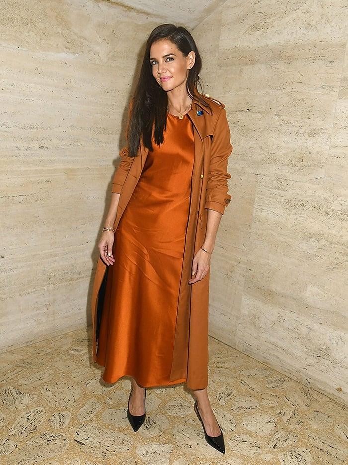Katie Holmes in an orange slip dress and matching Altuzarra trench coat