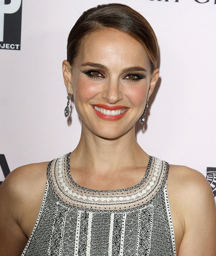 Natalie Portman pulls her hair into a tight bun and wears crimson lipstick and smoky eye-makeup