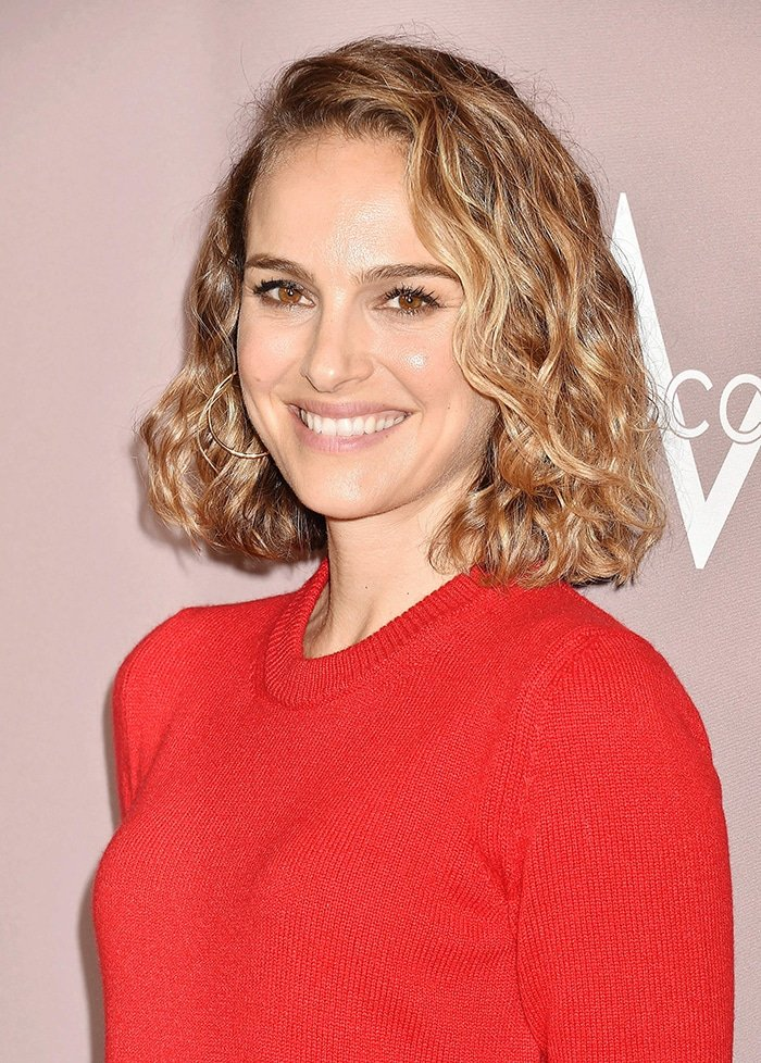 Natalie Portman wears her hair in side-swept curls and sports nude makeup