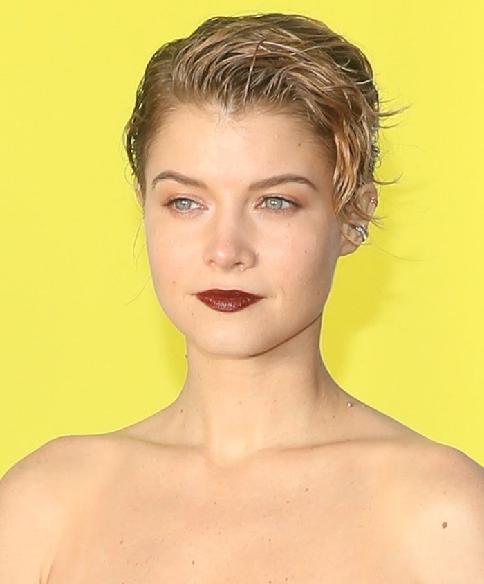 Sarah Jones wears short messy hair with off-center parting and bold red lipstick