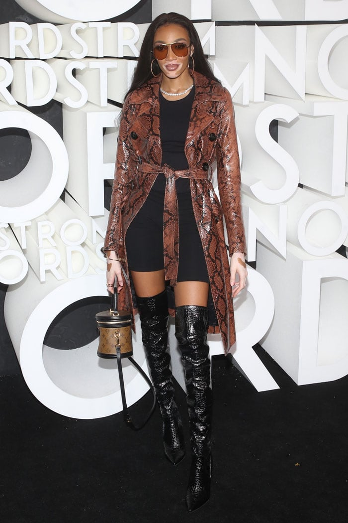 Winnie Harlow wearing a snakeskin trench coat, black croc-embossed thigh-high boots, and a Louis Vuitton Cannes handbag