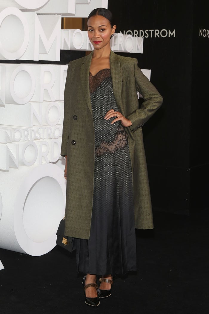 Zoe Saldana wearing an army-green Fendi coat, a lace-trimmed, black ombré pleated dress, Fendi patent neoprene Mary-Jane pumps, and a Fendi 'Kan U' small bag