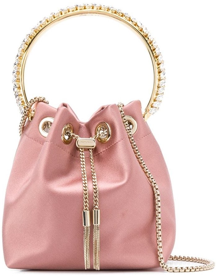 Crafted from blush pink silk, the Bon Bon bag boasts a gold-tone drawstring fastening and crystal embellishments