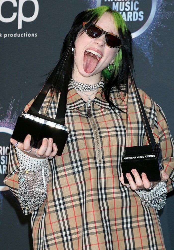 Billie Eilish sticks her tongue out as she shows off her two AMA trophies