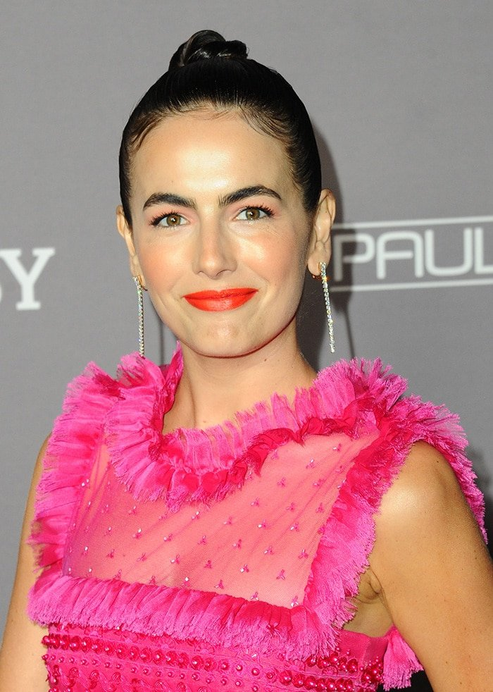 Camilla Belle pulls her hair in a bun and wears orange-red lip shade