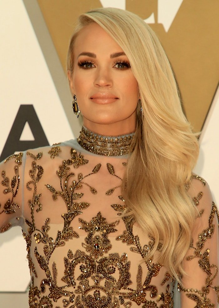 Carrie Underwood wears her blonde hair in side-swept waves and sports nude lipstick with smoky eye-makeup