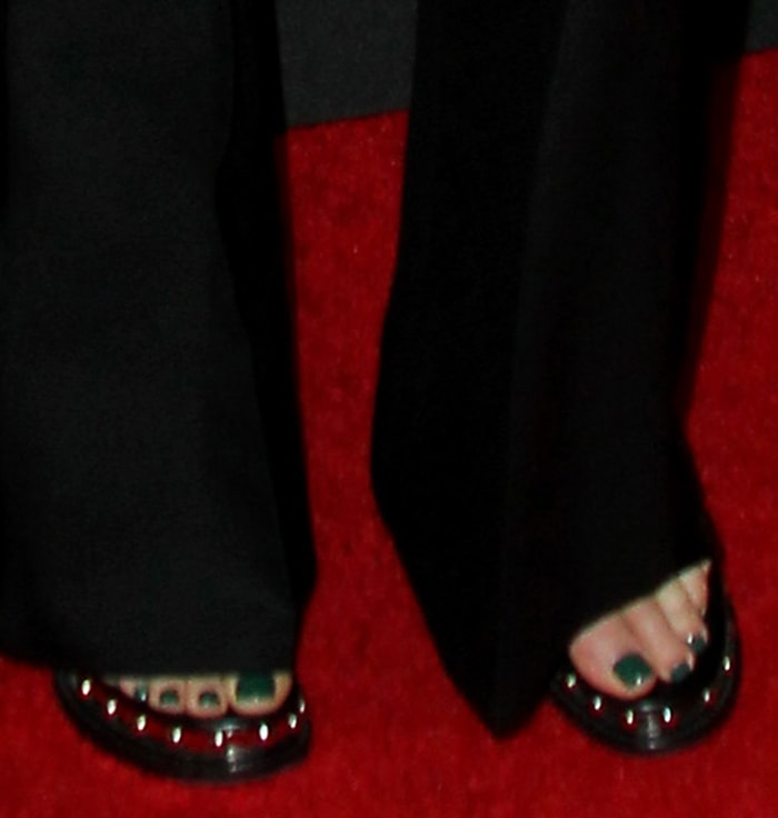 Charlize Theron shows her emerald pedicure in Alexander McQueen sandals