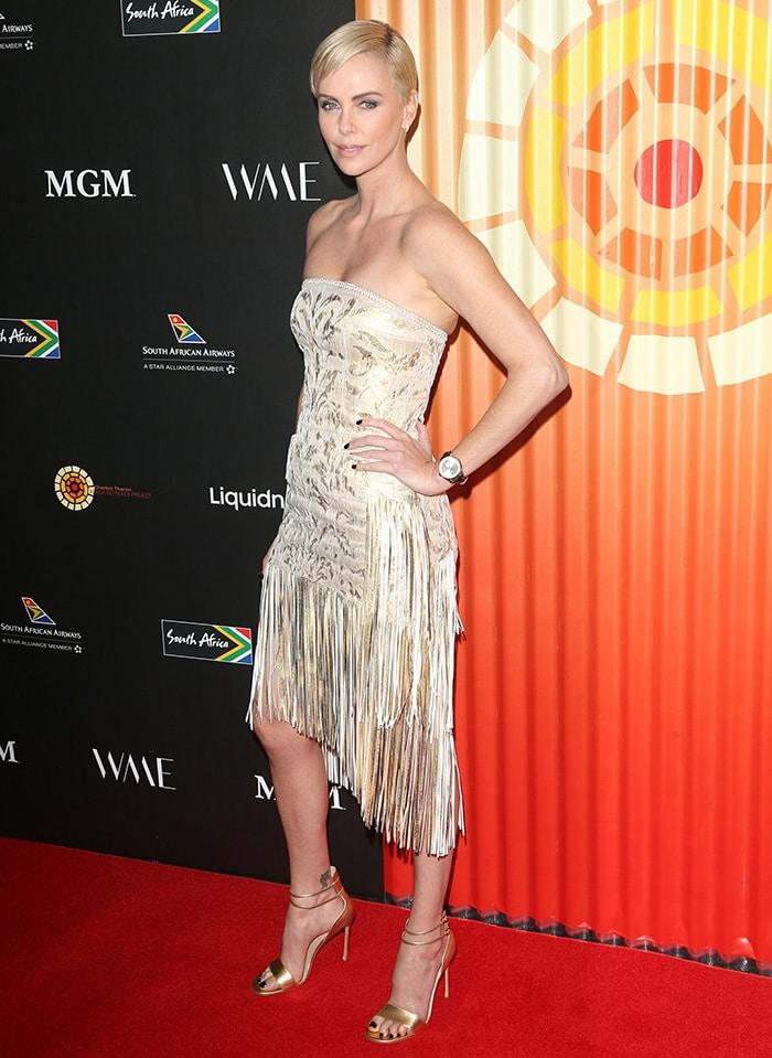 Charlize Theron wears a custom Dior gold mini dress