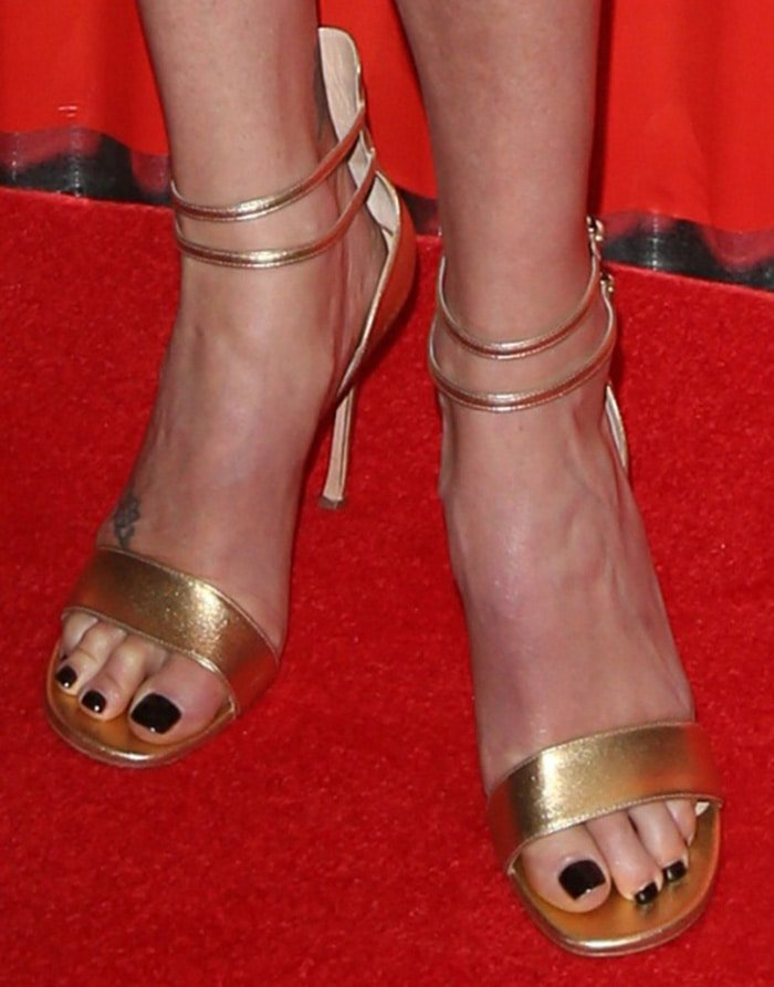 Charlize Theron shows her black nail polish in gold open-toe sandals