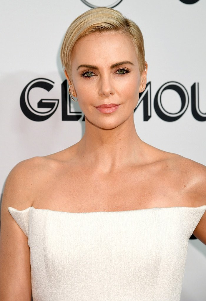 Charlize Theron wears dark liner and pink lipstick with her slicked pixie