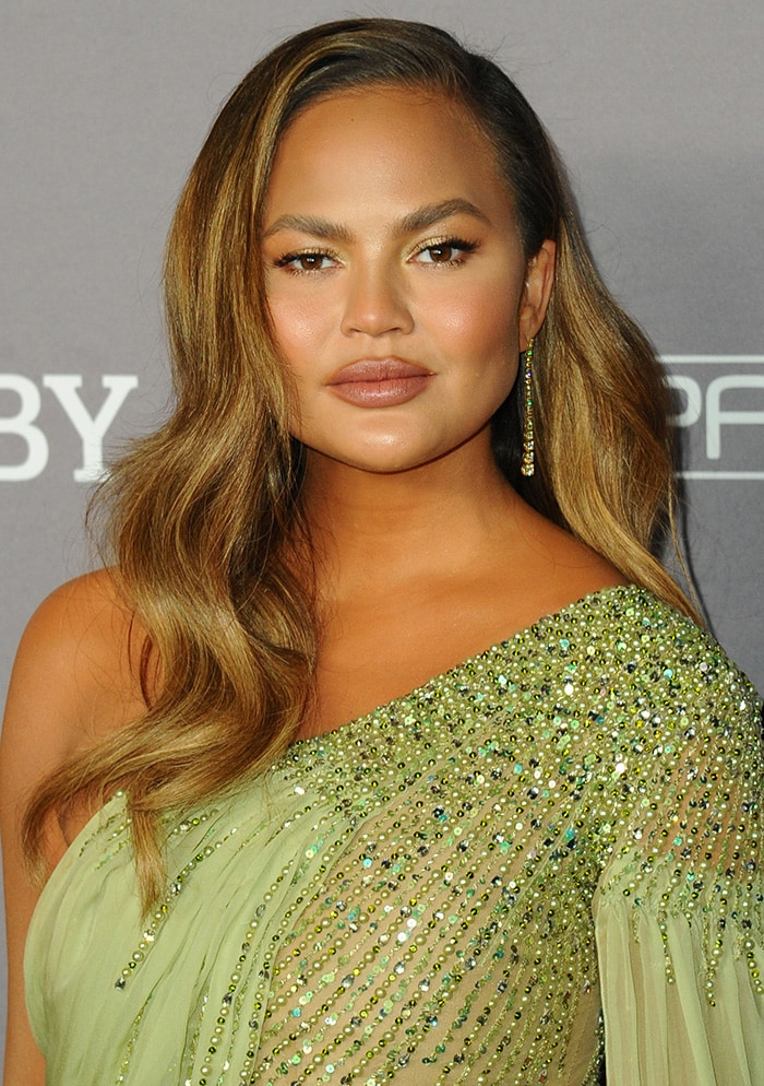 Chrissy Teigen wears her long hair in waves and sports makeup in natural palette