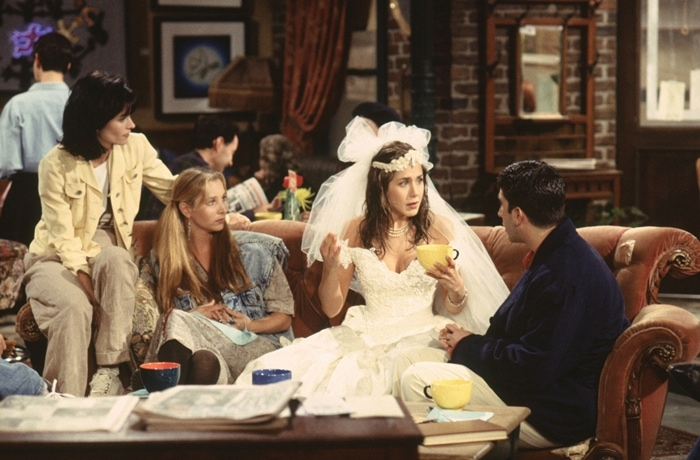 """Courtney Cox (as Monica Geller), Lisa Kudrow (as Phoebe Buffay), Jennifer Aniston (as Rachel Green), and David Schwimmer (as Ross Geller) in the first episode of Friends titled """"The Pilot"""" (also known as """"The One Where It All Began"""", """"The One Where Monica Gets A Roommate"""" and """"The First One""""), which premiered on September 22, 1994"""