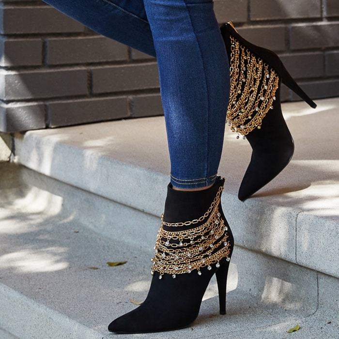 A pointed-toe bootie featuring a chain-link detail, stiletto heel, and back zipper closure