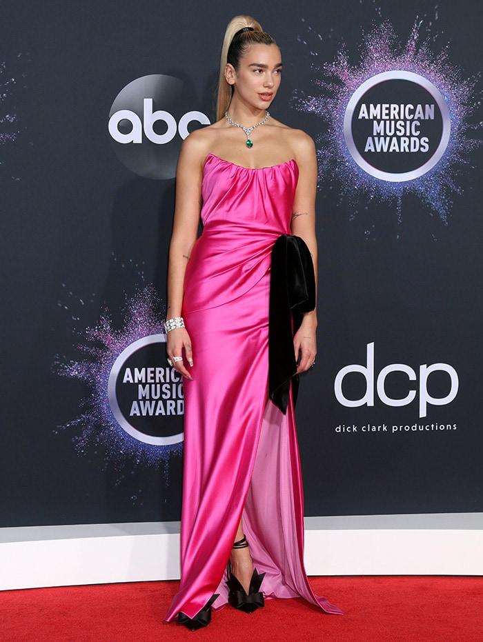 Dua Lipa shows a hint of cleavage in a pink Miu Miu gown