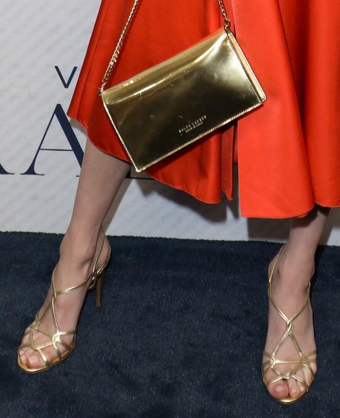 Emma Roberts carries a gold Ralph Lauren clutch and slips her sexy feet into matching gold sandals