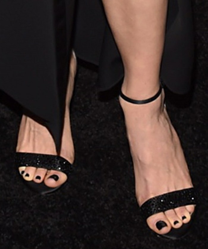 Emmy Rossum displays black nail polish in crystal-embellished open-toe sandals