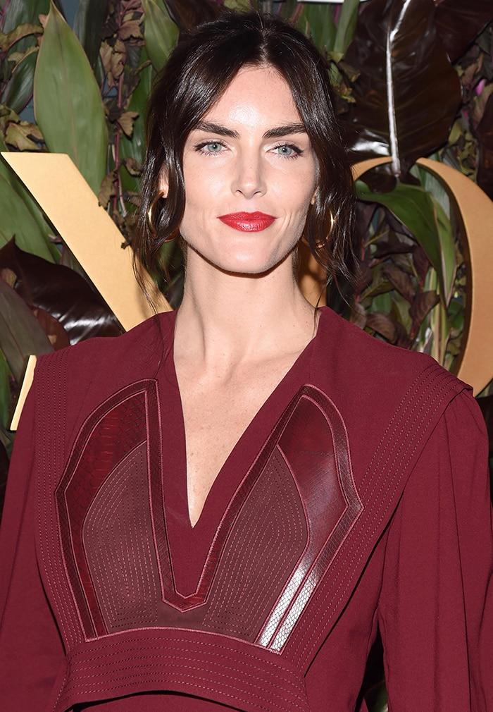 Hilary Rhoda wears bold red lipstick to match her dress