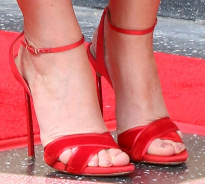 Idina Menzel slips into a pair of coordinating red Casadei sandals