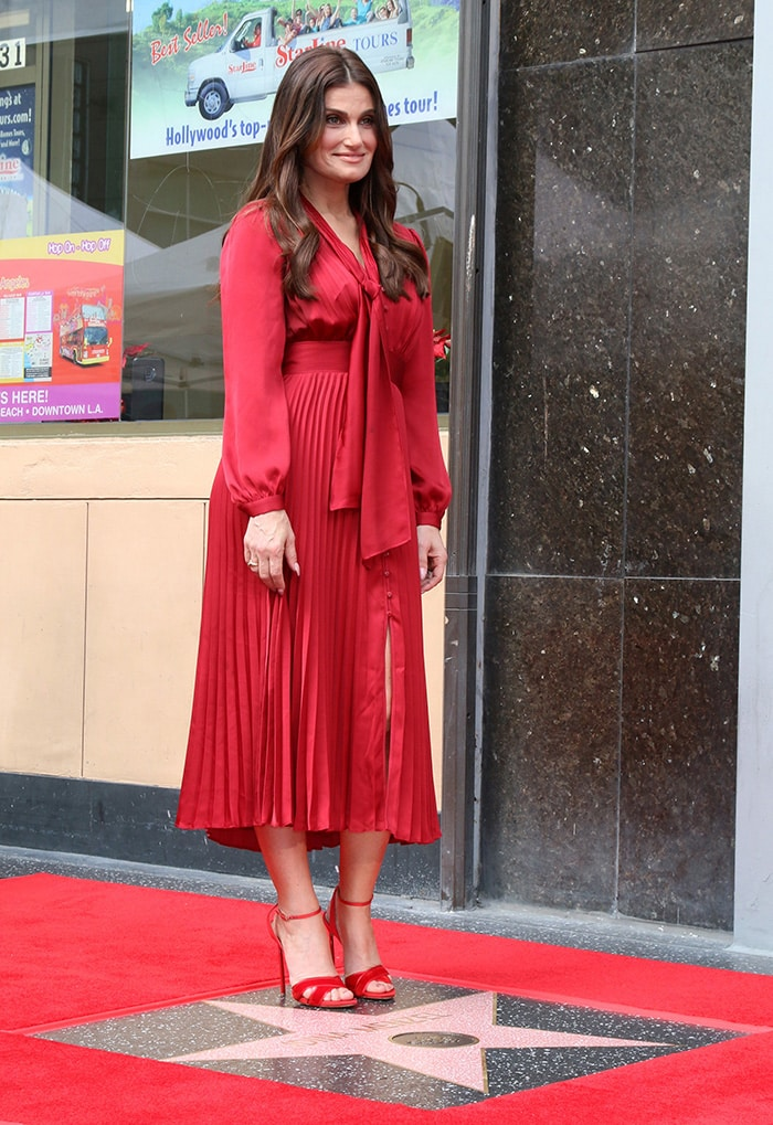 Idina Menzel wears a ruby red Equipment pleated dress