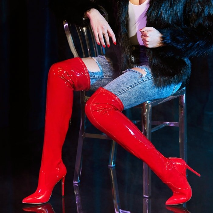 An over-the-knee boot featuring a pointed toe, sky-high stiletto, and back zipper closure